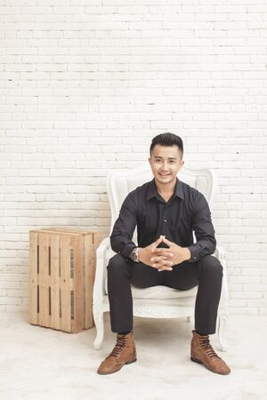 casual men: full view portrait of casual asian young man looking at camera while sitting at decorated room on white wall background