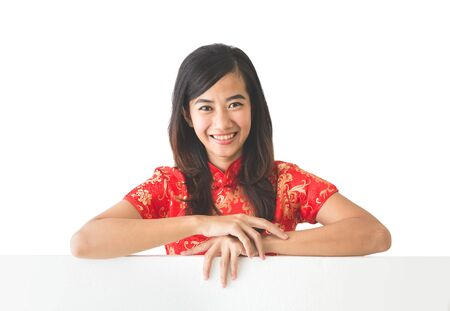 chinese dress: portrait of pretty asian woman wearing traditional chinese dress holding blank white board Stock Photo