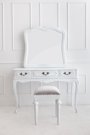 portret van vintage kaptafel set met kruk en spiegel op witte gevormde muur Stockfoto