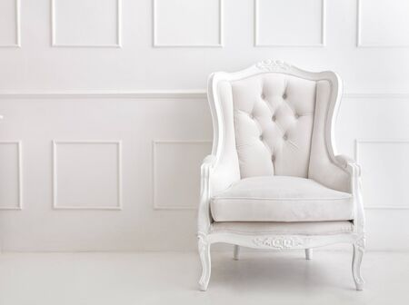 portrait of white vintage style armchair on white patterned wall with copy space