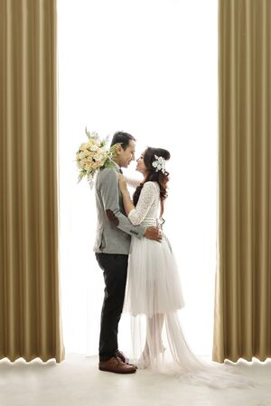 soulmate: full body portrait of romantic asian newlywed couple embracing each other on white background with curtain