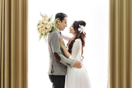 white wedding: portrait of romantic asian newlywed couple embracing each other on white background with curtain