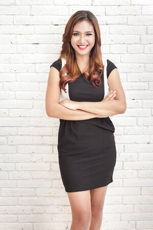 blank screen: portrait of beautiful woman wearing casual black and white dress smiling with armcrossed on white brick wall background Stock Photo