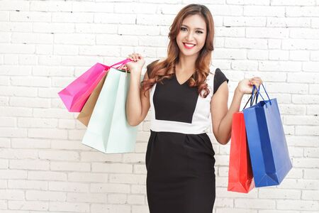 happy shopping: portrait of happy elegant woman carrying multicolor shopping bags on white brick wall background