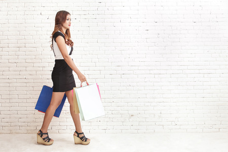 hang body: full body portrait of woman in black and white dress walking while carrying shopping bags Stock Photo