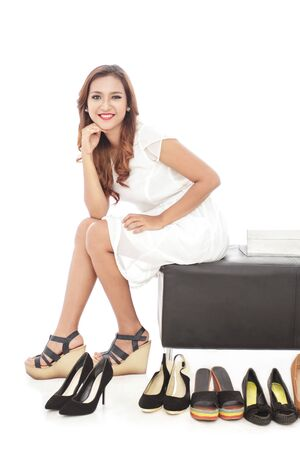 beautiful woman body: full body portrait of elegant woman smiling and sitting next to pairs of shoes isolated on white background