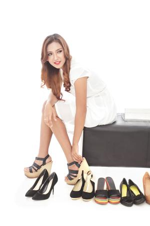 persona sentada: retrato de cuerpo entero de una mujer joven que intenta en varios pares de zapatos nuevos aislados sobre fondo blanco