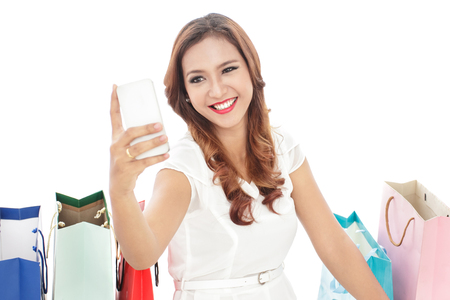 mobilephone: attractive young woman taking selfie photo with mobilephone while sitting between shopping bags isolated on white background