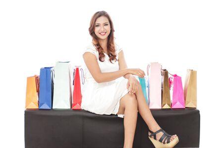 chicas de compras: retrato de la hermosa mujer sentada en el sofá entre bolsas aisladas sobre fondo blanco