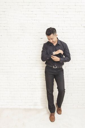 man shirt: full body portait of casual asian man standing while fixing his shirt sleeve at decorated room with white wall background