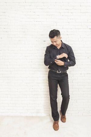 cuerpo hombre: Portait de todo el cuerpo del hombre asiático casual de pie mientras que la fijación de la camisa de manga en habitación decorada con el fondo de la pared blanca