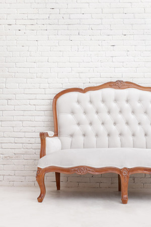 wall design: portrait of White classical style sofa on white brick wall with cropping