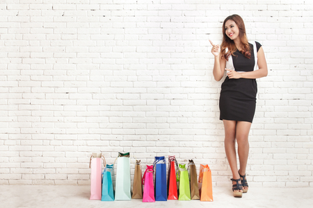 흰색 벽돌 벽 배경에 복사본 공간을 가리키는 동안 쇼핑 가방 옆에 서있는 아름 다운 젊은 여자의 전신 초상화 스톡 콘텐츠