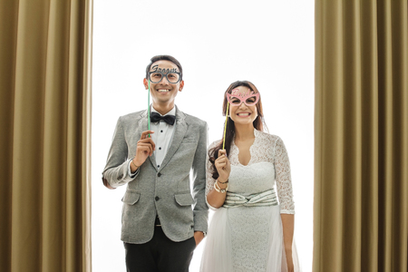 portrait of funny moments of newlywed asian couple on white background with curtain