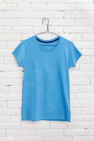 camicia appesa blu sul muro di mattoni bianchi Archivio Fotografico