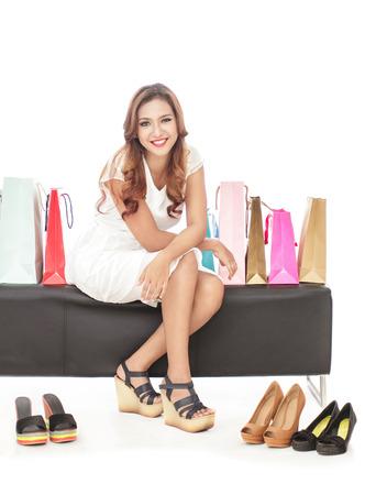 comprando zapatos: Retrato de cuerpo entero de la mujer de compras atractiva que se sienta entre los bolsos y los pares de zapatos aislados en el fondo blanco