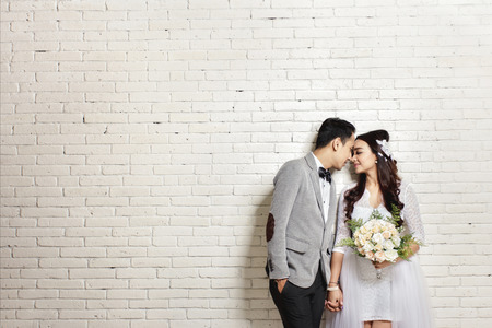 prewedding: portrait of lovely asian newlywed couple with copy space on white wall background