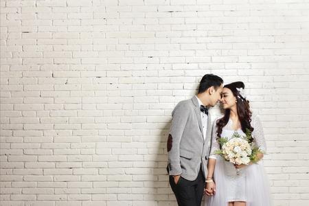 portret van mooie Aziatische pasgetrouwde stel met een kopie ruimte op een witte muur achtergrond Stockfoto