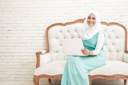 hijab: portrait of smiling asian young woman wearing hijab sitting on sofa while working on laptop at home with copy space