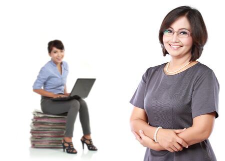 friendly: A portrait of a mature business women standing with her secretary behind holding a laptop on her lap Stock Photo
