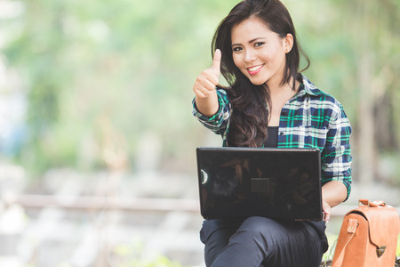 A portrait of a young asian woman using laptop while sitting on the park and showing thumb up Imagens