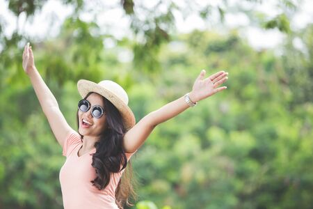 hot day: A portrait of a beautiful young asian woman wearing round hat on a park