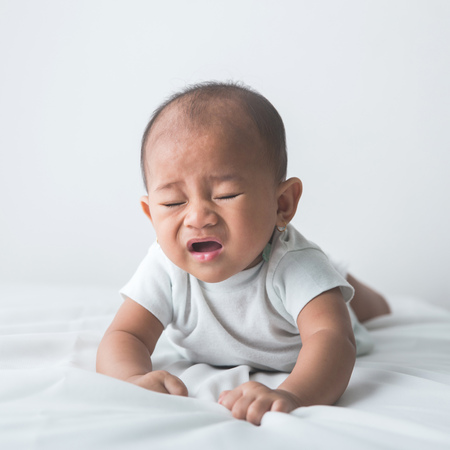 fever: portrait of a cute baby sneezing while tummy time Stock Photo