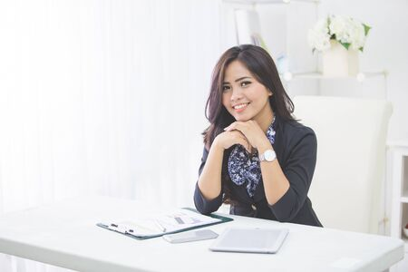 business woman working: Young smiling business woman working on her paperwork in her office Stock Photo