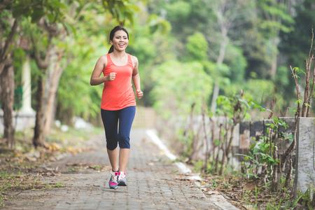 アジアを行う若い女性、公園の屋外運動ジョギングの肖像画