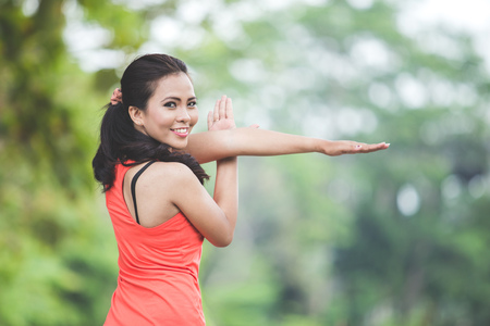 A portrait of a young asian woman doing excercise outdoor in a park, stretching