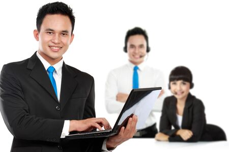 team from behind: A portrait of a young caucasian businessman, with his team behind holding laptop. isolated in white background