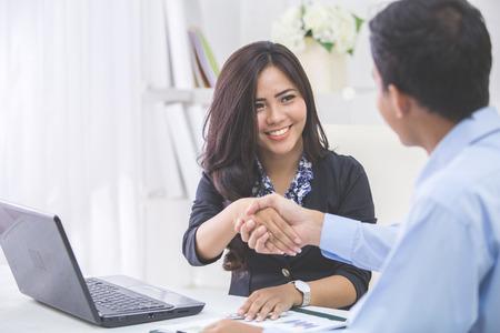 business: 亞裔俏麗的女商人在會議期間握手商人的手在她的辦公室