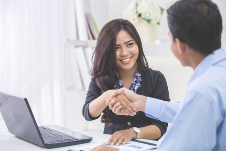 business  deal: Pretty asian business woman shaking hands with businessman in her office during meeting