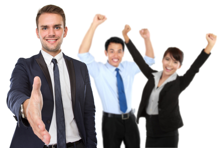 raise hand: A portrait of businessman offering hand shake while happy team raise hand at the background