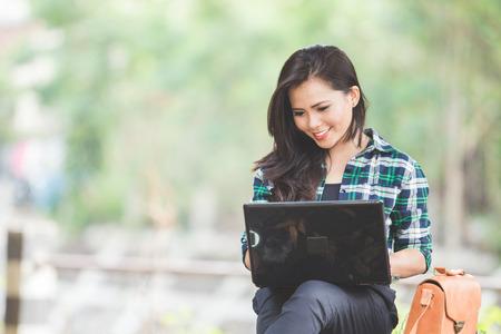Een portret van een jonge Aziatische vrouw met behulp van laptop zittend op het park