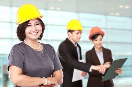 reunion de trabajo: retrato de mujer de negocios llevar un casco de seguridad. con el equipo disccussing en el fondo