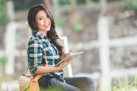 Un retrato de una mujer asiática joven con un Tablet PC mientras está sentado en el parque