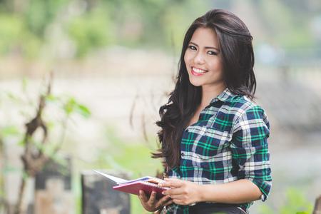 sonrisa: Un retrato de una joven asiática leyendo un libro en el parque