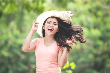 Een portret van een mooie jonge Aziatische vrouw, gekleed in round hoed op een park