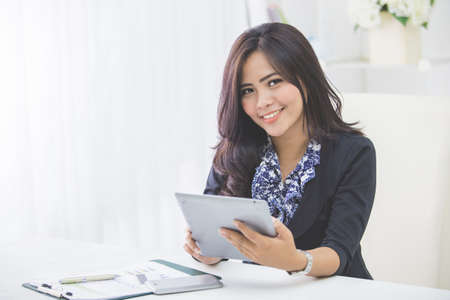 tab: smiling business woman using tablet pc while sitting in the office