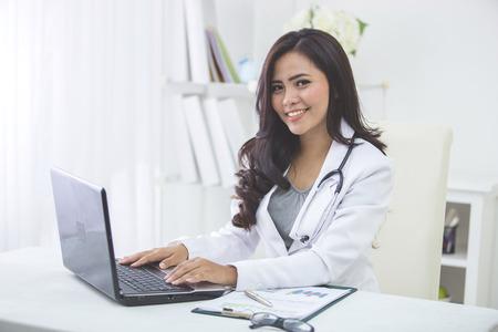 glimlachende Aziatische vrouwelijke arts die op kantoor werkt