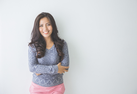 human arm: Asian woman leaning on a white wall. Casual woman crossed arm smiling looking happy in grey sweater