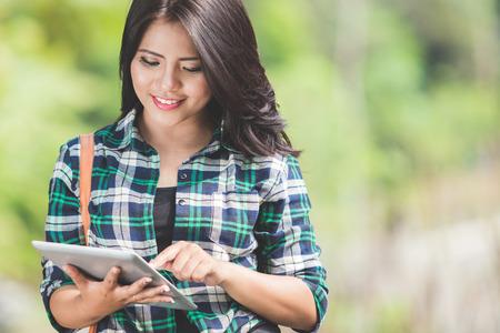 Un portrait d'une jeune femme asiatique en utilisant un Tablet PC tout en marchant sur le parc