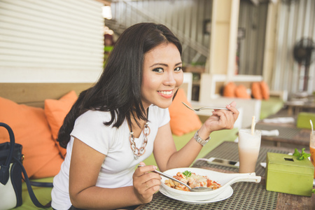 one woman: A portrait of a young beautiful asian woman in a restaurant, enjoying her food