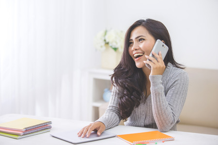 portrait of casual asian woman making a phone call at home using smart phone Foto de archivo