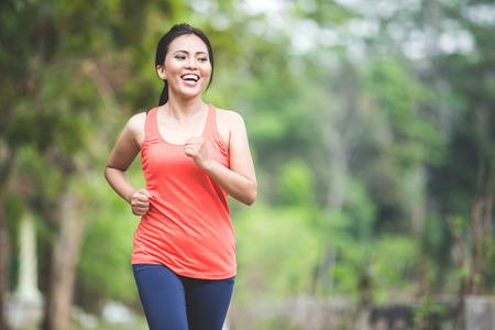 Un retrato de una mujer asiática joven haciendo ejercicio al aire libre en un parque, correr