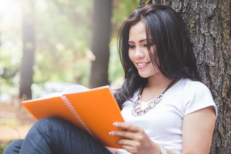 mujer leyendo libro: Un retrato de una mujer asiática joven que lee un libro al aire libre en un parque Foto de archivo
