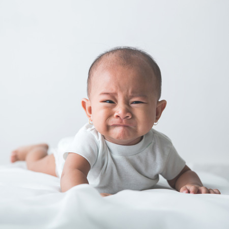 portrait of unhappy baby crying out loud