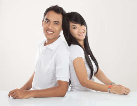 A portrait of young Asian couple sitting together, smiling to the camera
