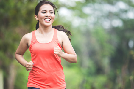 A portrait of a young asian woman doing excercise outdoor in a park, jogging
